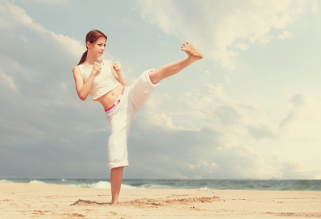 athletic woman performing a kick in an sand beach photo