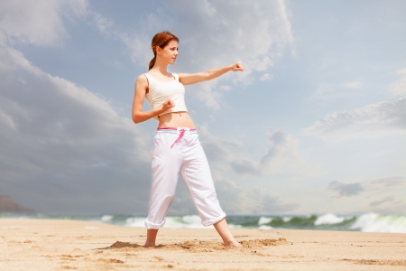athletic woman performing a exercise in an sand beach photo