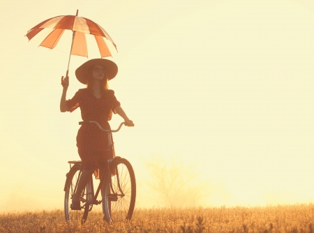 Girl with umbrella on a bike in the countryside in sunrise time photo