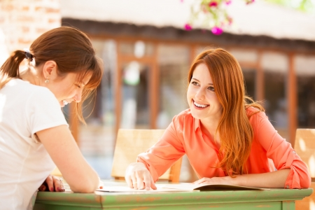 Two girls sitting in the cafe and looking in menu. photo