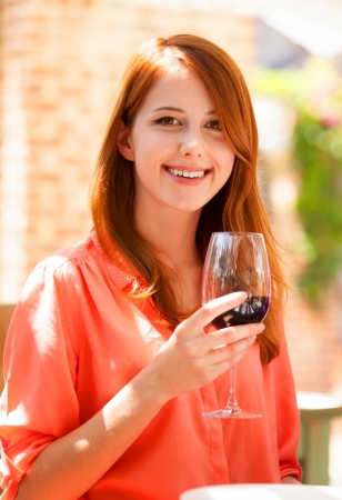 Redhead girl with glass of wine in the cafe photo
