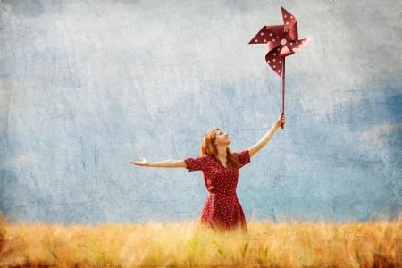 the enchantress: Redhead girl with toy wind turbine Stock Photo
