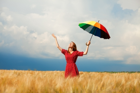 Redhead girl with umbrella at field photo