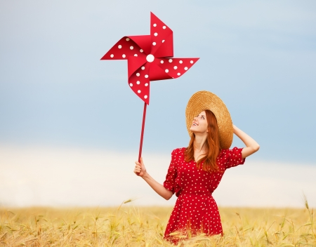 Redhead girl with toy wind turbine Фото со стока