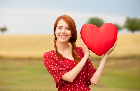 Redhead girl with toy heart at meadow near wheat field photo
