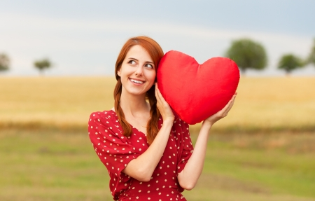 the enchantress: Redhead girl with toy heart at meadow near wheat field