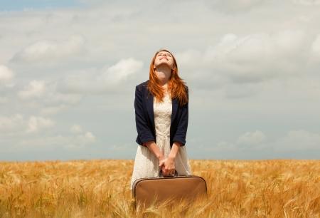 mujer con maleta: Chica pelirroja con maleta en campo de trigo de primavera. Foto de archivo