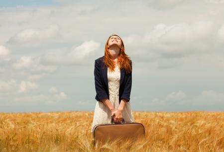 vintage dress: Redhead girl with suitcase at spring wheat field. Stock Photo