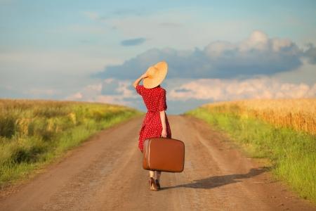 krajina: Zrzka dívka s kufrem na venkovní.