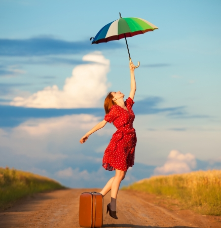 enchantress: Redhead girl with umbrella and suitcase at outdoor