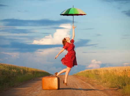 Redhead girl with umbrella and suitcase at outdoor