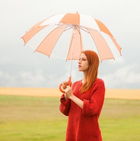 the enchantress: Redhead girl with umbrella at meadow Stock Photo