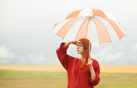 Redhead girl with umbrella at meadow photo