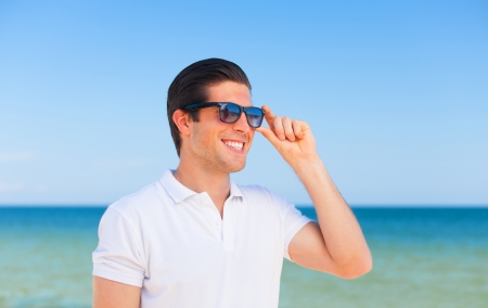 Handsome young man at beach background photo