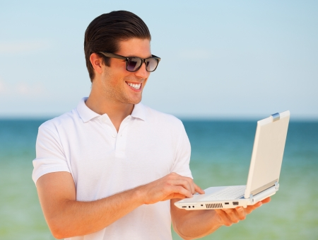 Handsome young man with laptop at beach background photo
