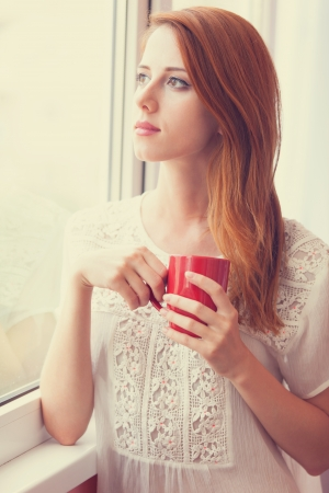 Beautiful young woman with cup over window.  photo