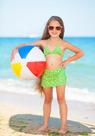 child with sunglasses and ball at the beach photo
