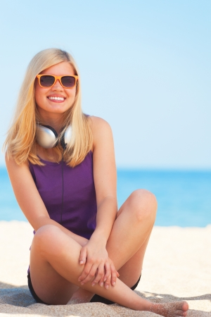 Portrait of blonde girl with headphone on the beach. photo
