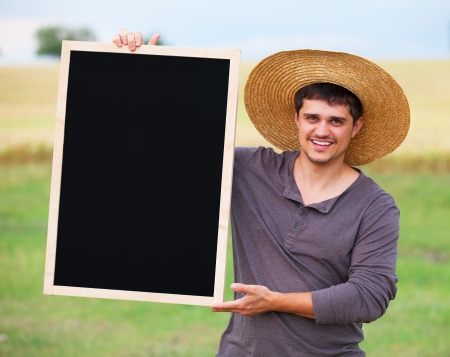 Farmer with blackboard at wheat field. photo