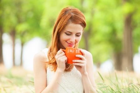 mujer tomando cafe: Chica pelirroja con la taza de color naranja en el exterior Foto de archivo