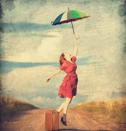 mujer con maleta: Chica pelirroja con paraguas y maleta en el exterior Foto de archivo