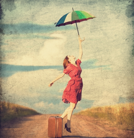 woman with umbrella: Redhead girl with umbrella and suitcase at outdoor