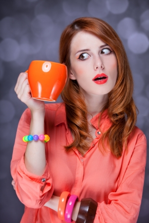 Redhead girl with cup. Studio shot. photo