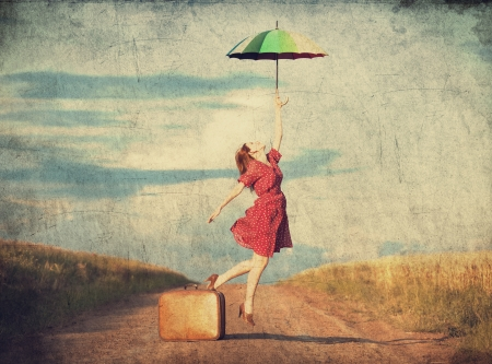 Redhead girl with umbrella and suitcase at outdoor photo