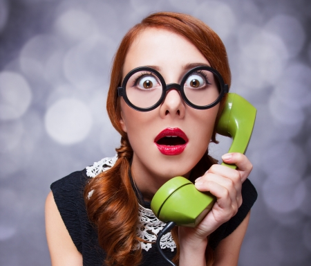 緑電話で赤毛の女性。 写真素材