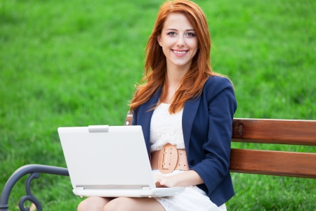 Redhead girl sitting at the bench with notebook photo