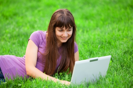 Brunette girl at green grass with notebook photo
