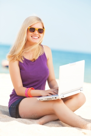 Blonde girl with notebook at the beach. photo