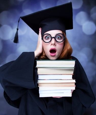 graduating student girl in an academic gown with books photo