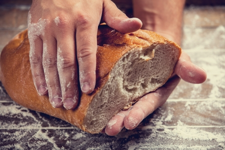 Bakers hands with a bread. Photo with high contrast photo