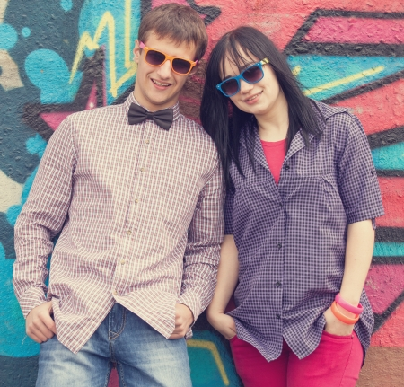 Style teen couple near graffiti background. photo