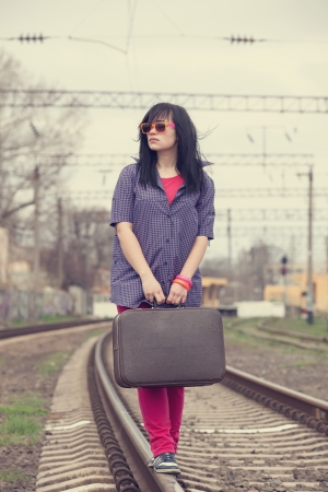 Young fashion girl with suitcase at railways. Stock Photo - 21111715