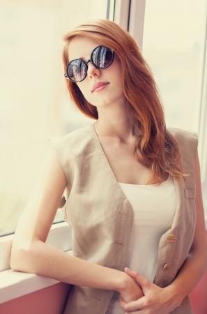 Grunge girl in sunglasses near window photo