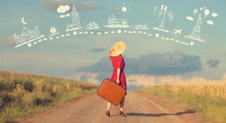 reizen: Roodharige meisje met koffer bij outdoor.
