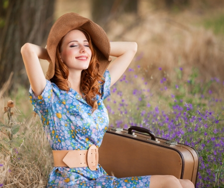 redhaired: Redhead girl with suitcase sitting at autumn grass