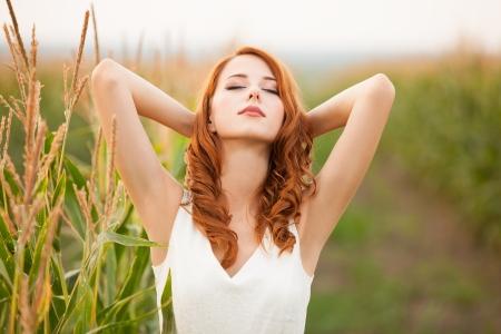 Roodharige meisje in maïsveld Stockfoto