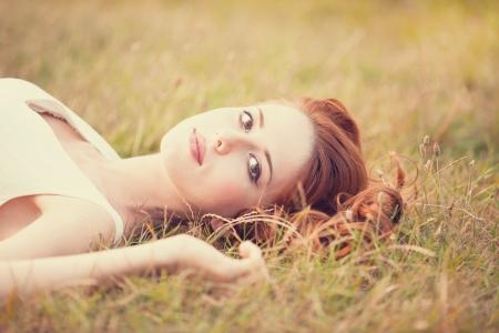 girl lying down: Chica pelirroja acostado en la hierba Foto de archivo