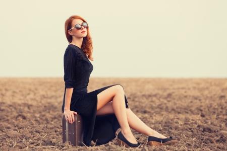 mujeres fashion: Moda mujer pelirroja con maleta en el campo de otoño