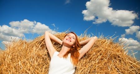 Redhead girl lying down on hay Stock Photo