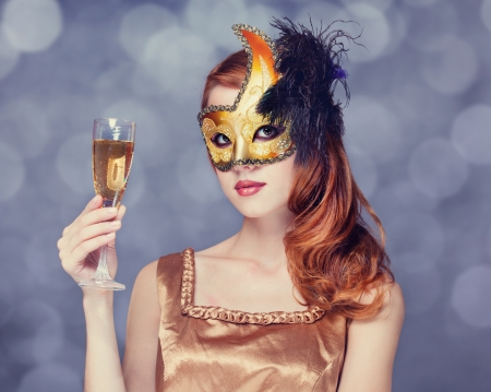 Redhead women in mask with champagne photo