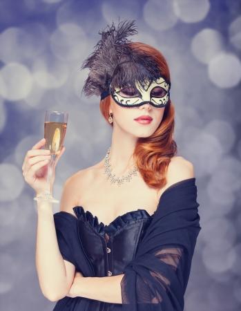Mujer pelirroja en la máscara con champán Foto de archivo - 21697743
