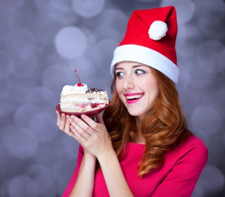 Redhead girl in christmas hat with cake photo
