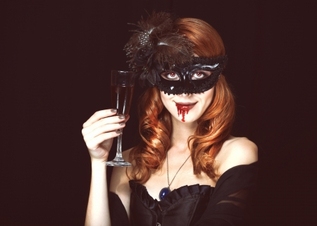 Redhead vampire woman in mask with glass of blood. Photo in vintage style. photo