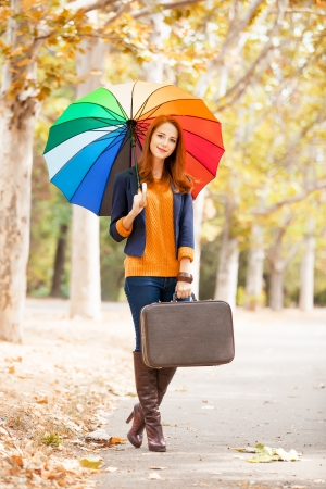 Girl with suitcase and umbrella at autumn outdoor photo