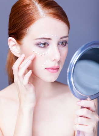 Beauty face of young redhead women with cosmetic cream on a cheek and mirror photo