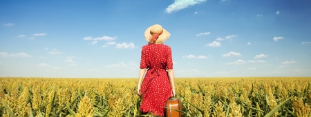 Redhead girl with suitcase at corn field.